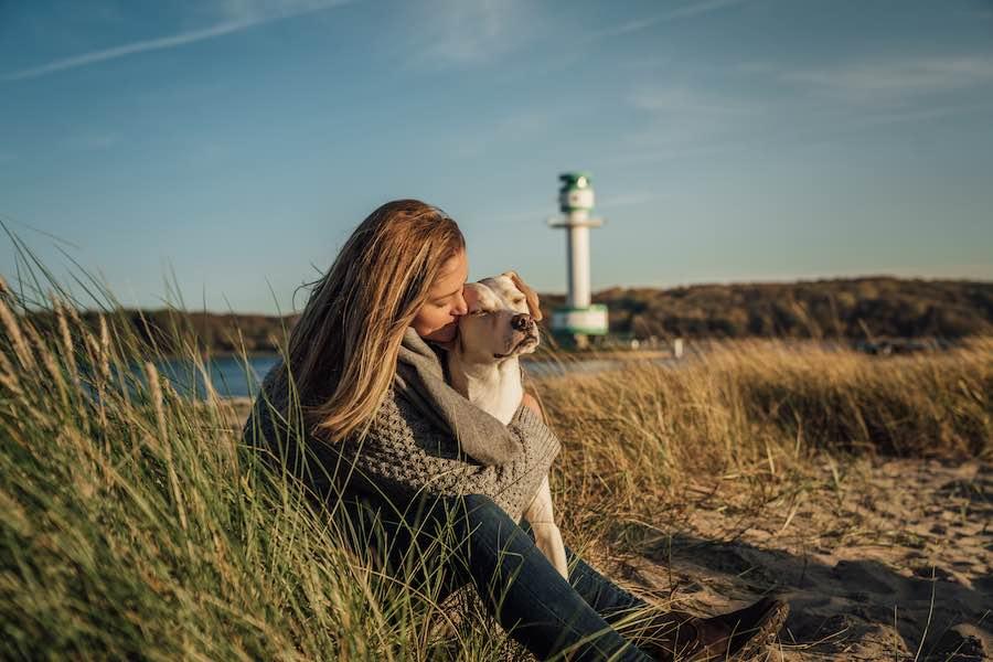 Hund und Frau sind entspannt am Strand